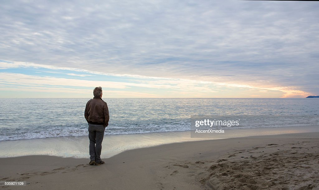 Man stands on beach under dome of clouds : Stock Photo