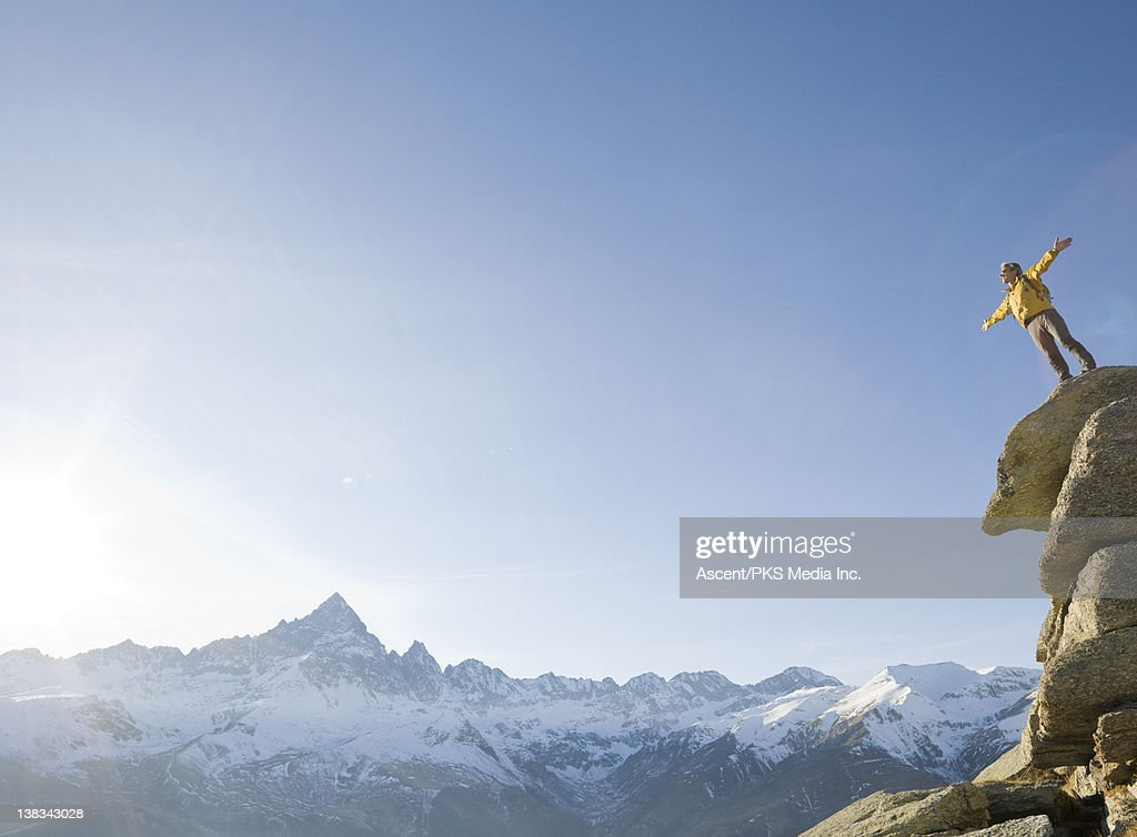 Man stands on cliff edge, arms outstretched : Stock Photo