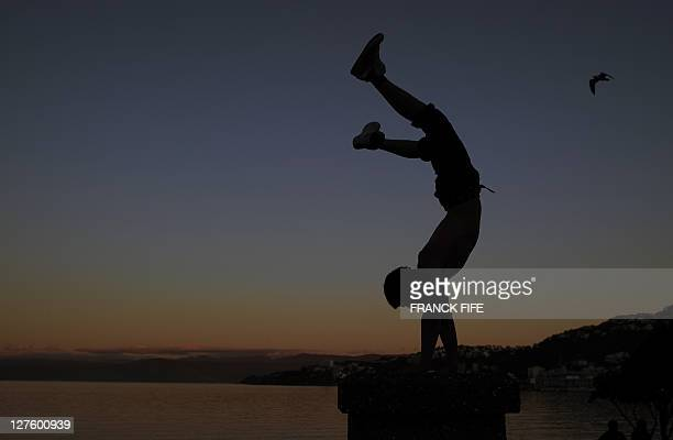 A man stands on his hands by the sea in Wellington on September 30 during the 2011 Rugby World Cup in New Zealand AFP PHOTO / FRANCK FIFE