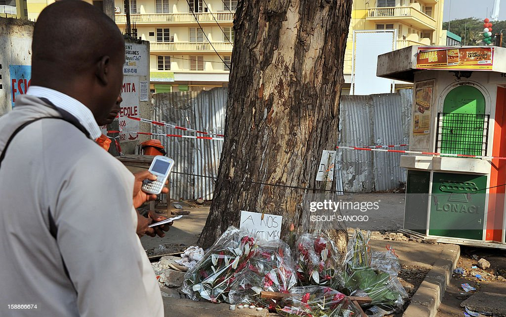 A man stands on January 2, 2013 by flowers laid at a tree in the street of Abidjian where at least 60 persons died in a stampede among crowds gathered for celebratory New Year's Eve fireworks that also left dozens injured. Ivory Coast began today three days of national mourning.