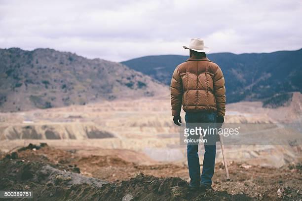 Homme se dresse sur mound de travail site admirer les montagnes