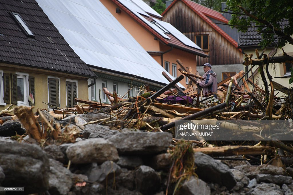 A man stands on of rubbish laying in a flooded street in Braunsbach, southern Germany, on May 30, 2016. Four people died and several more were injured in southern Germany after violent storms with torrential rains caused severe flooding, authorities said. / AFP / dpa / Marijan Murat / Germany OUT