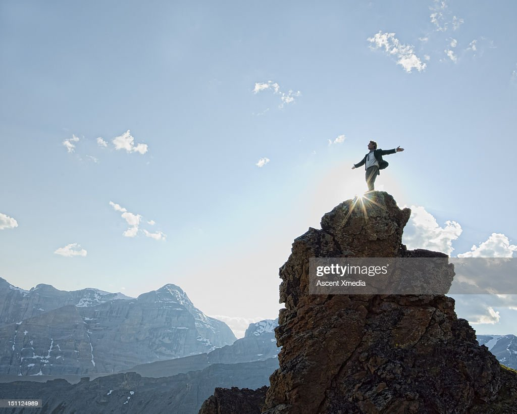 Man stands on peak, arms outstretched. : Stock Photo
