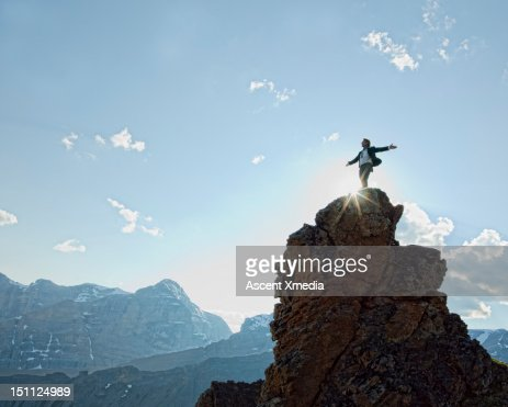 Man stands on peak, arms outstretched.