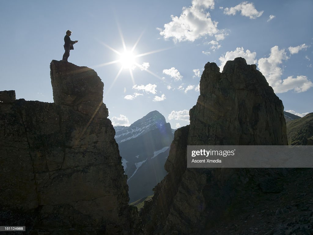 Man stands on peak, sends text. : Stock Photo