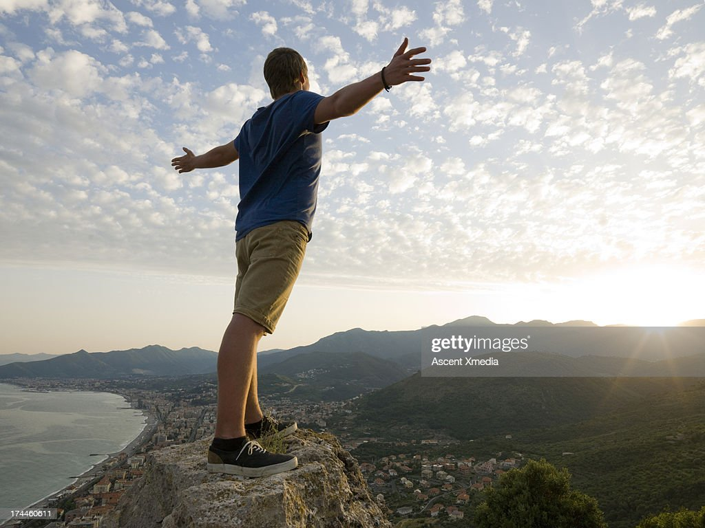 Man stands on rock above sea, outstretched arms