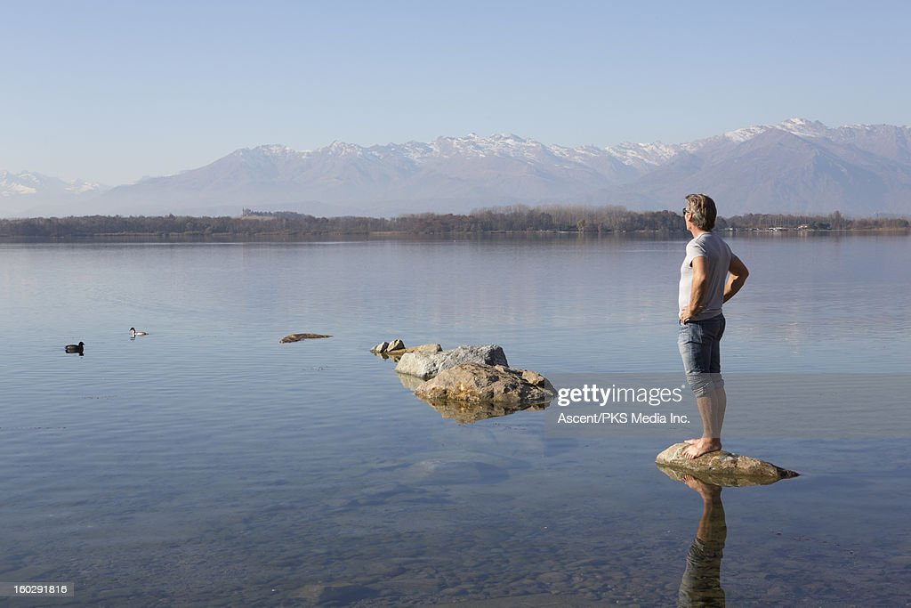Man stands on rock at mountain lake, looks off : Stock Photo