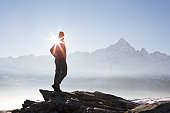 Man stands on rock bluff overlooking mtns, sunrise