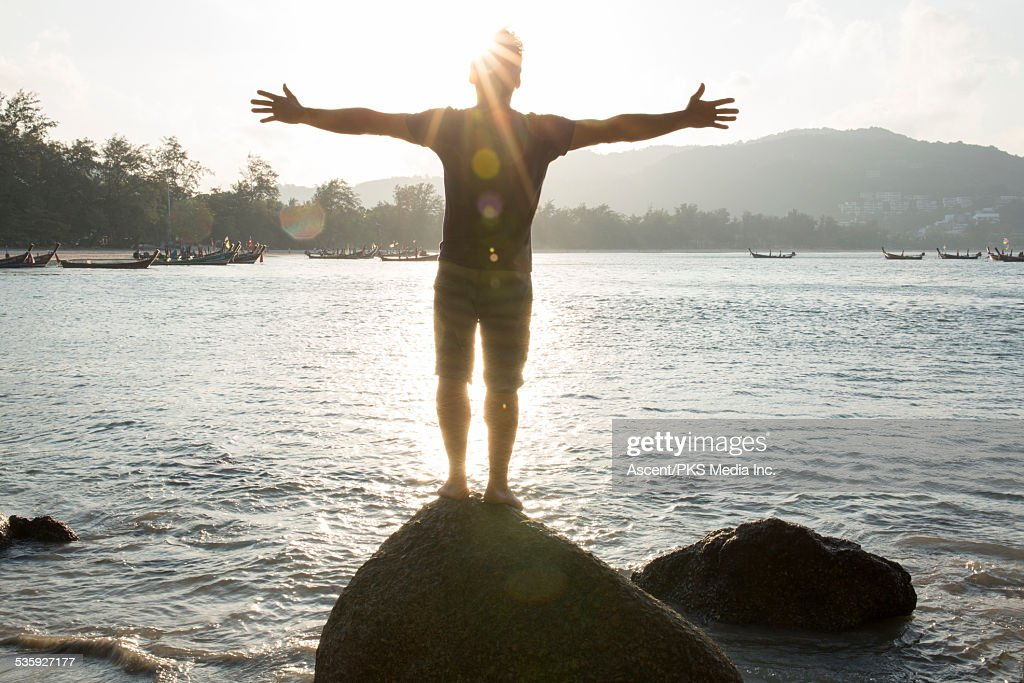 Man stands on rock overlooking sea, arms out : Stock Photo