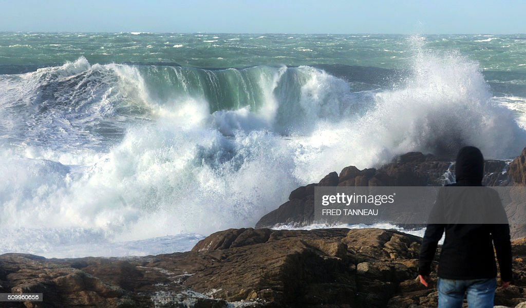 A man stands on rocks watching the crashing waves of the Atlantic ocean at Saint-Guénolé, western of France on February 13, 2016. / AFP / FRED TANNEAU