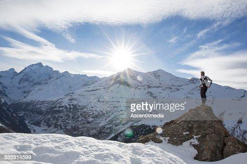 Man stands on summit of snowy peak, looks off : Stock Photo