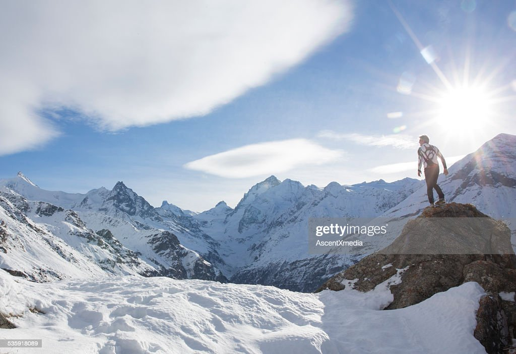 Man stands on summit of snowy peak, looks off : Stock Photo