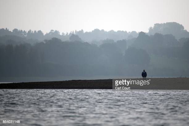 A man stands on the bank of the lake as he waits for the restored Blue Bird K3 hydroplane powerboat to undertake a test run at Bewl Water on...