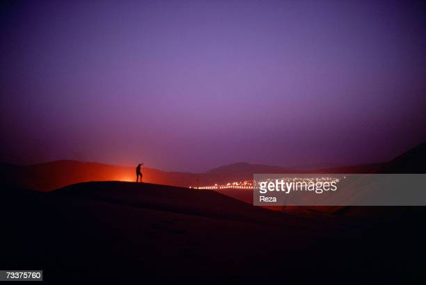 A man stands on the dunes at night just outside the Saudi Aramco oil field complex facilities at Shaybah in the Rub' al Khali desert on March 2003 in...