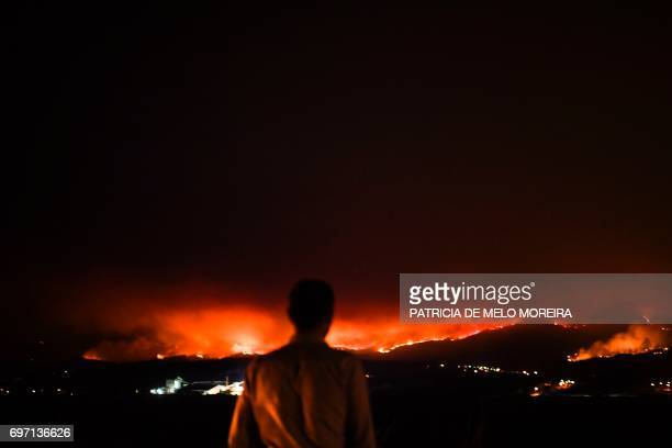 TOPSHOT A man stands on the roadside and watches a wildfire at Anciao Leiria central Portugal on June 18 2017 A wildfire in central Portugal killed...