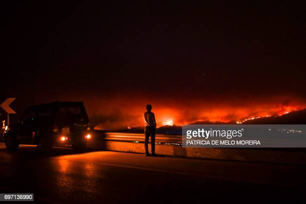 A man stands on the roadside watching a wildfire at Anciao Leiria central Portugal on June 18 2017 A wildfire in central Portugal killed at least 25...