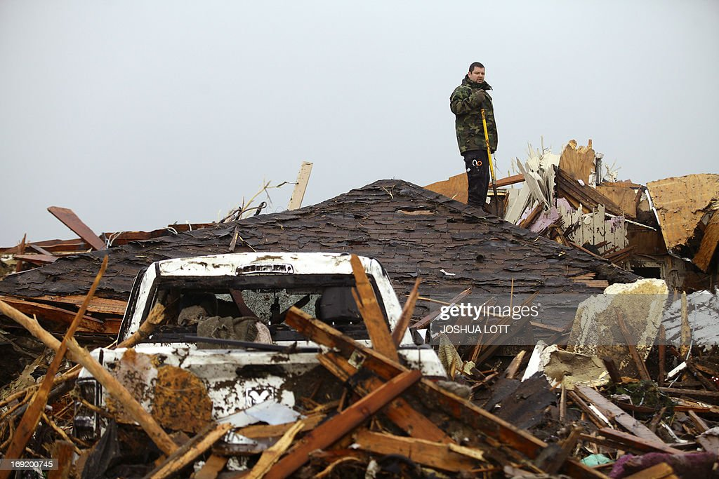 A man stands on the roof of a destroyed home on May 21, 2013 in Moore, Oklahoma. Families returned to a blasted moonscape that had been an American suburb Tuesday after a monstrous tornado tore through the outskirts of Oklahoma City, killing at least 24 people. Nine children were among the dead and entire neighborhoods vanished, with often the foundations being the only thing left of what used to be houses and cars tossed like toys and heaped in big piles. AFP PHOTO/Joshua LOTT