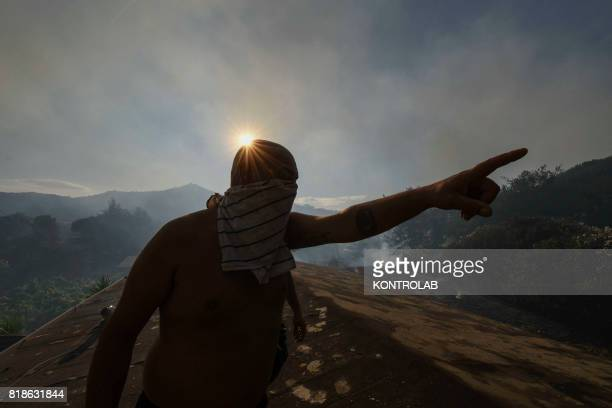 A man stands on the roof of his house and look towards smoke on the horizon during a vast fire that threatened the inhabited areas between Naples and...