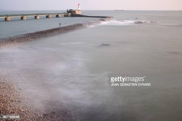 A man stands on the sea wall at the Port of Les Sablesd'Olonne western France as they wait for a high tide on March 21 2015 The exceptionally high...