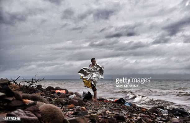 A man stands on the shore as refugees and migrants arrive on the Greek Lesbos island after crossing the Aegean Sea from Turkey on October 22 2015 An...