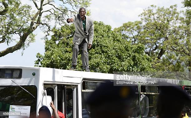A man stands on the top of a packed bus after learning that we would not be able to board to pay his respect to South African former president Nelson...