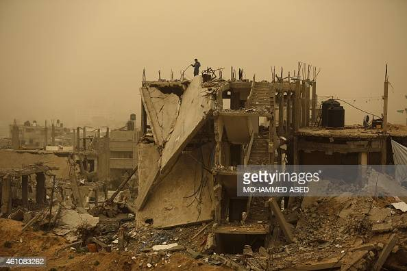 A man stands on top of a building destroyed in the 50day Gaza war between Israel and Hamasled militants during a winter storm in Gaza City's...