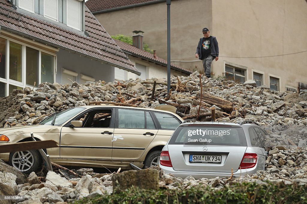 A man stands on top of rubble and two smashed cars that cover a street in the village center following a furious flash flood the night before on May 30, 2016 in Braunsbach, Germany. The flood tore through Braunsbach, crushing cars, ripping corners of houses and flooding homes during a storm that hit southwestern Germany. Miraculously no one in Braunsbach was killed, though three people died as a result of the storm in other parts of the country.