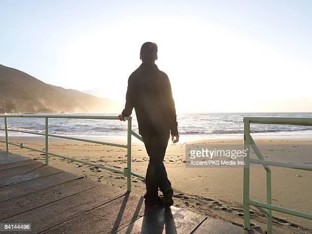 Man stands on wooden deck, looks out to sea