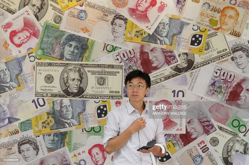 A man stands outside a foreign exchange outlet in Hong Kong on June 28, 2016. Hong Kong stocks ended slightly lower on June 28, unable to match an Asian rebound from last week's Brexit-fuelled selloff because of its exposure to Europe-linked companies. / AFP / ANTHONY