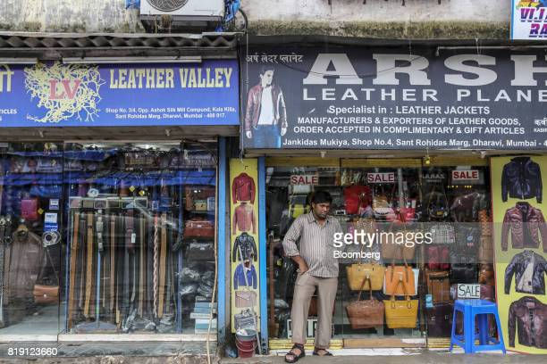 A man stands outside a leather goods store in the Dharavi area of Mumbai India on Tuesday July 18 2017 India's new goods and services tax introduced...