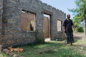 A man stands outside his family home of over 40 years which was burnt during a recent eviction Land grievances date back to Kenya's independence when...