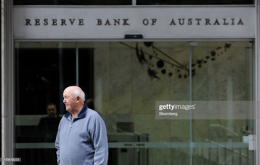 A man stands outside the Reserve Bank of Australia (RBA) headquarters in the central business district of Sydney, Australia, on Monday, July 15, 2013. While the RBA previously needed higher interest rates to control price pressures as the Australian economy expanded since 1991 without a recession, Governor Glenn Stevens has slashed the cash target, predicting a mining boom will wane. Photographer: Dan Himbrechts/Bloomberg via Getty Images