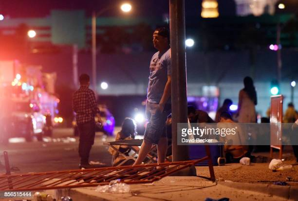 A man stands outside the the Route 91 Harvest country music festival grounds after an active shooter was reported on October 1 2017 in Las Vegas...
