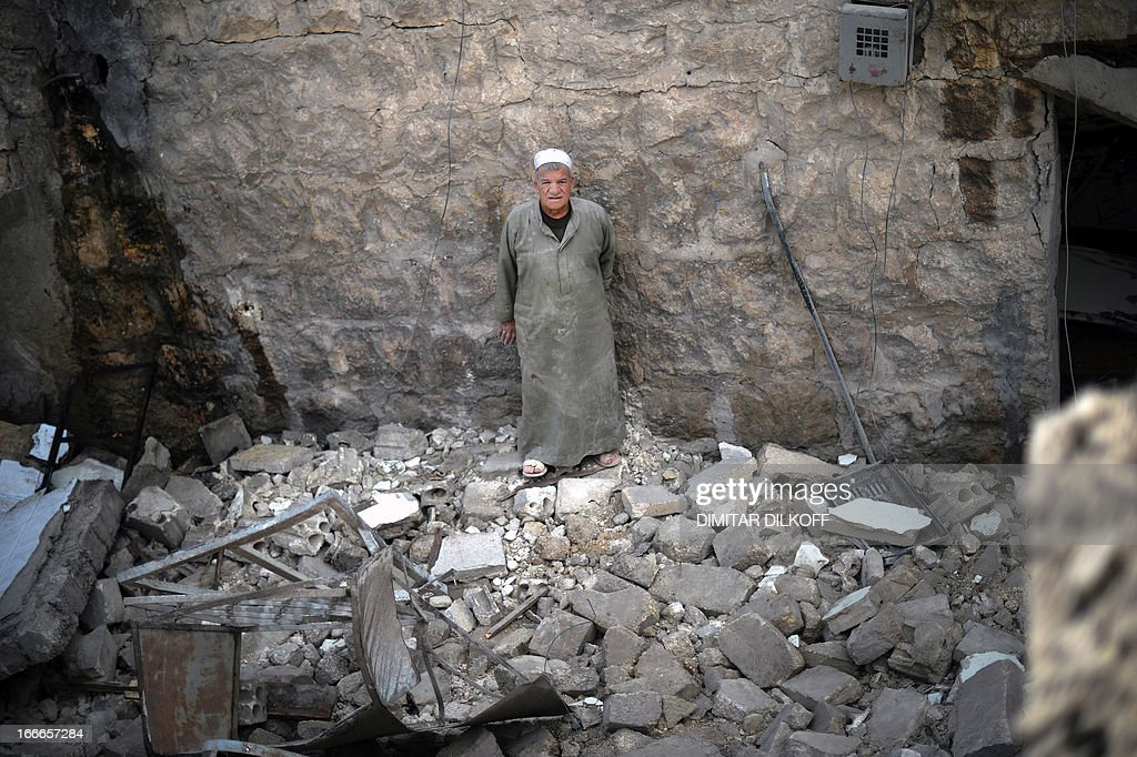 A man stands shocked in the remains of a house following an airstrike by the Syrian airforce in the northern Syrian city of Aleppo on April 15, 2013. The conflict in Syria, which is now in its third year, has cost 70,000 lives, according to the United Nations.