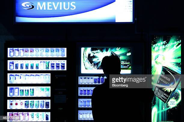 A man stands silhouetted in front of a vending machine selling Japan Tobacco Inc cigarettes in Tokyo Japan on Wednesday Feb 4 2015 Japan Tobacco the...
