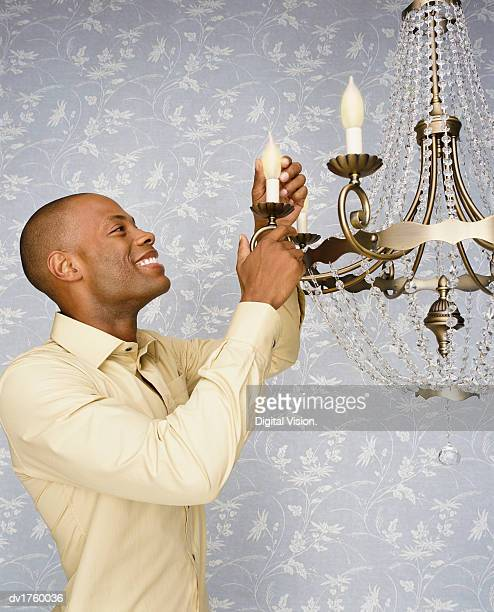 Man Stands Smiling as He Changes a Lightbulb on a Chandelier