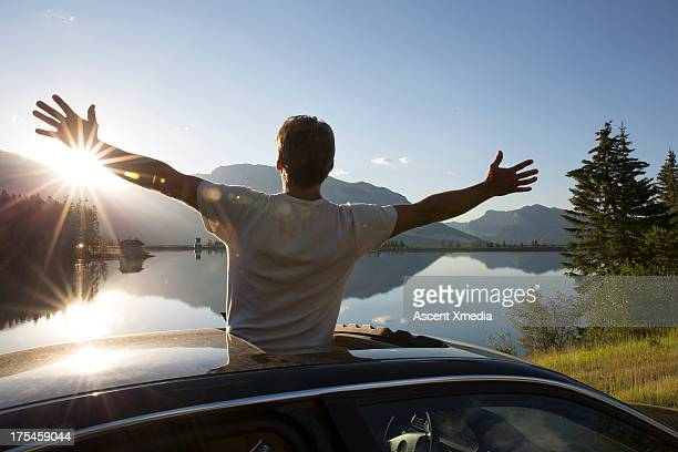 Man stands through car sunroof, spreads arms wide