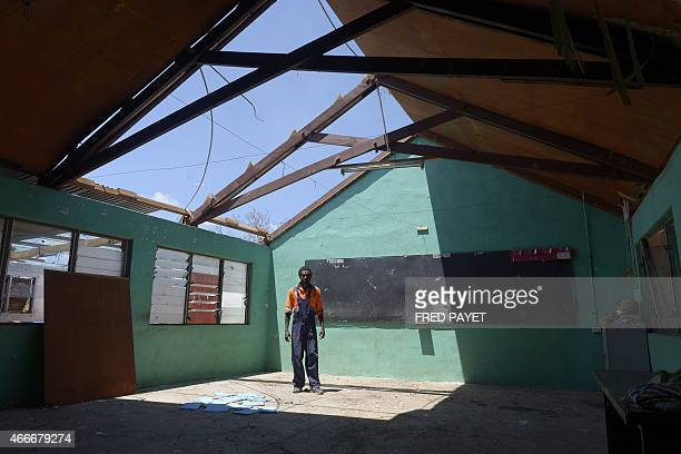 A man stands under the partially damaged rooftop of a school in Port Vila on March 18 2015 after Severe Tropical Cyclone Pam hit the Pacific nation...