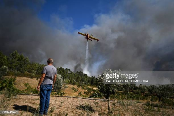 TOPSHOT A man stands watching a firefighter plane dropping water on a wildfire at Macao on August 17 2017 / AFP PHOTO / PATRICIA DE MELO MOREIRA
