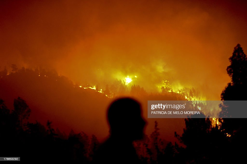 A man stands watching a wildfire in Santiago de Besteiros, near Caramulo, central Portugal, early on August 30, 2013. Five Portuguese mountain villages were evacuated overnight as forest fires intensified in the country's north and centre, officials said today. As many as 1,400 firefighters were dispatched Thursday to tackle the blaze in the mountains and another raging further north in the national park of Alvao, where 2,000 hectares (4,900 acres) of pine forest have already been destroyed, according to the local mayor. AFP PHOTO / PATRICIA DE MELO MOREIRA