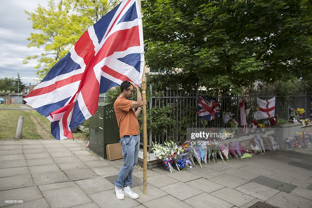 A man stands with a large union flag at the scene of fusilier Lee Rigby's murder adjacent to the Royal Artillery Barracks on the first anniversary of...