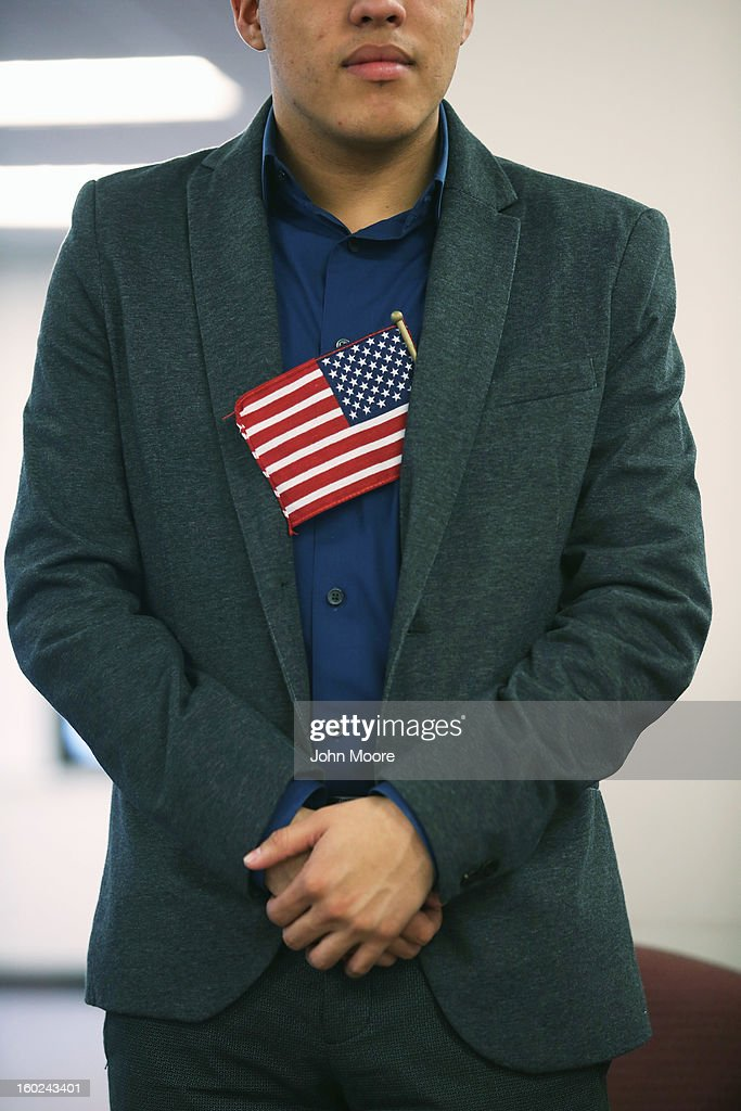 A man stands with an American flag in his jacket during a naturalization ceremony at the district office of U.S. Citizenship and Immigration Services (USCIS) on January 28, 2013 in Newark, New Jersey. Some 38,000 immigrants became U.S. citizens at the Newark office alone in 2012.