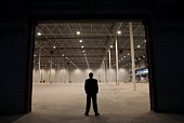 Man stands with hands in pockets at warehouse entrance