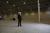 Man stands with hands in pockets in empty warehouse