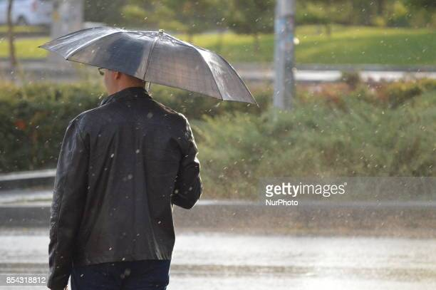 A man stands with his umbrella as he checks cars to walk across the road during a rainy autumn day in Ankara Turkey on September 26 2017 The...