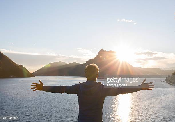 Man stands with outstretched arms over lake, sun