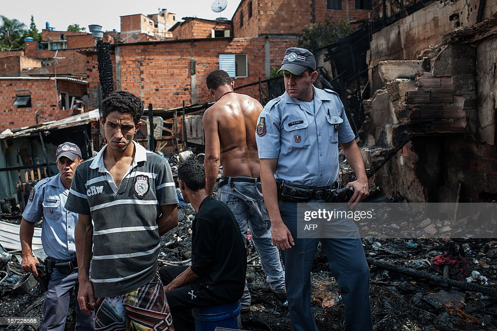 A man stands with police officers after losing his home by a fire at Paraisopolis shantytown in Sao Paulo, Brazil on November 30, 2012. According to the city's fire department, no casualty was reported and around 30 homes were burnt. AFP PHOTO/Yasuyoshi CHIBA