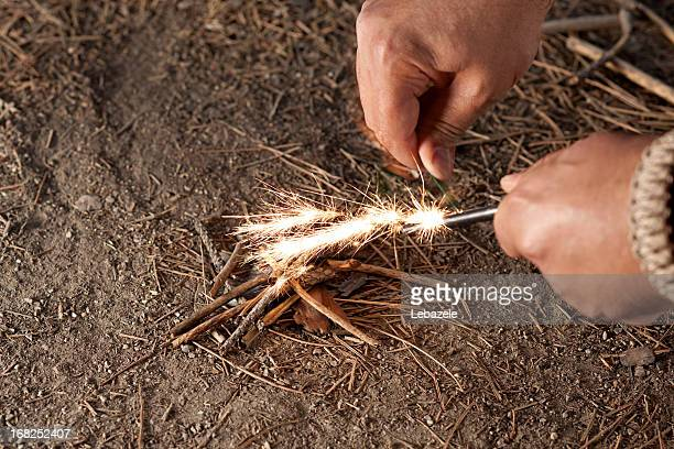 Man starting fire with ember and twigs