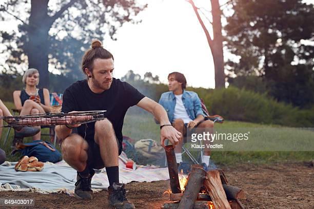Man starting up bonfire at campsite