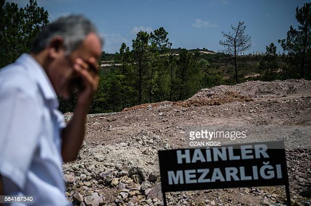 TOPSHOT A man stays next to a sign reading in Turkish language 'Traitors' Cemetery' is seen in front of unmarked graves built specially by Istanbul...